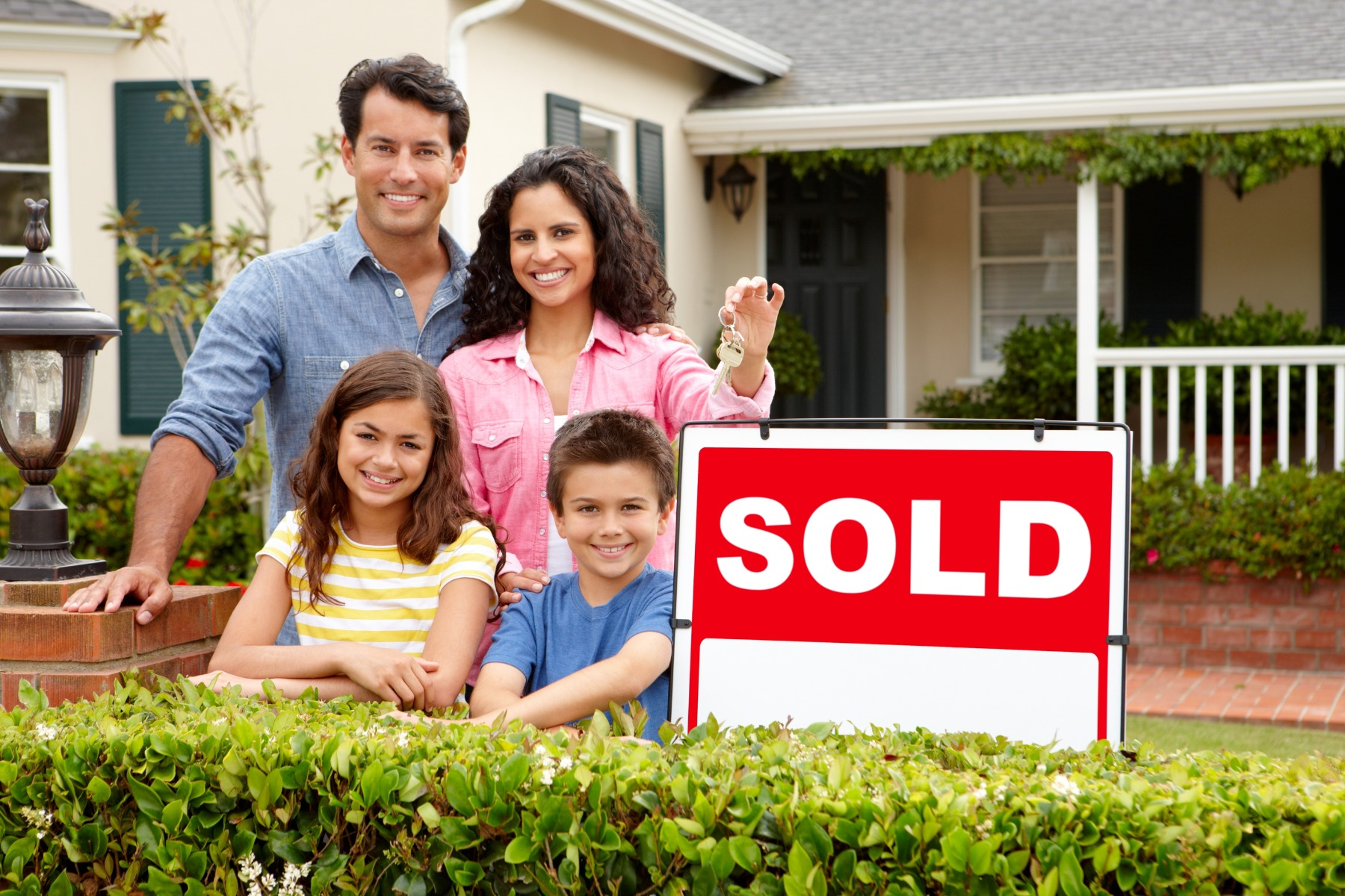 family in front of a house with sold sign