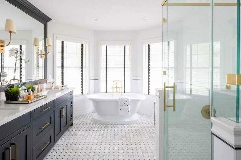 white bathroom with black cabinets, white bath, white tiles, glass shower screen