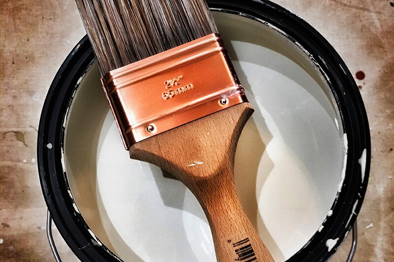 paint in can with brush - painting hack to minimize paint smell
