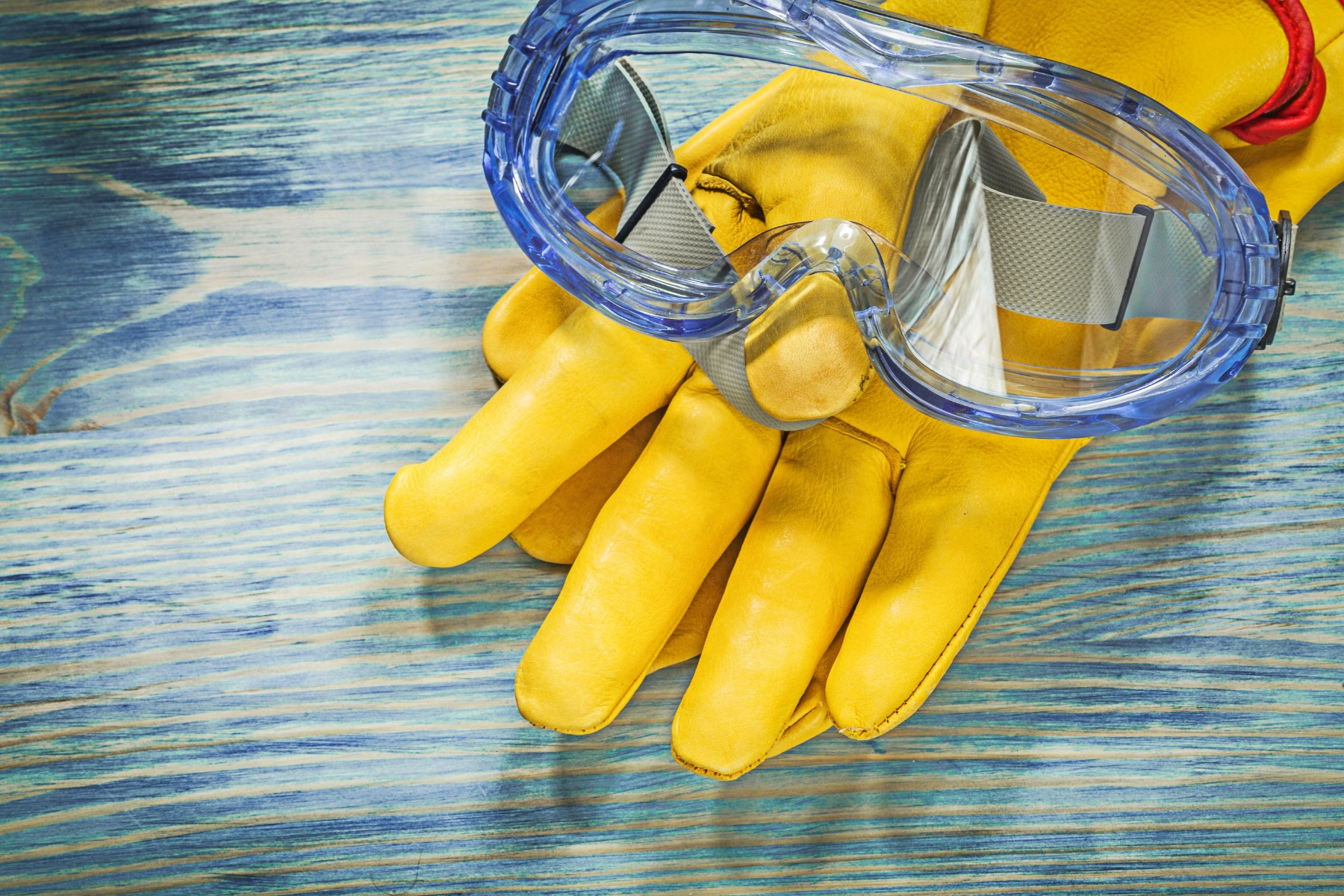 protective gloves and goggles on wooden board construction