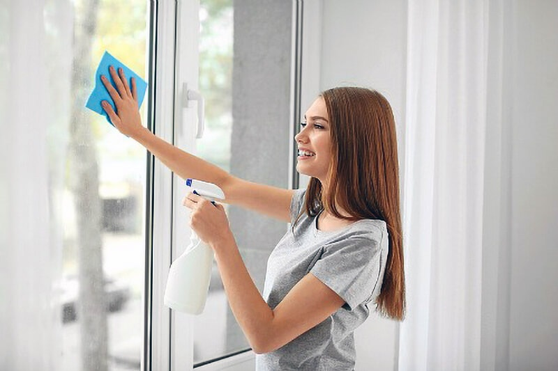 woman wiping window glass with blue cloth and sprayer
