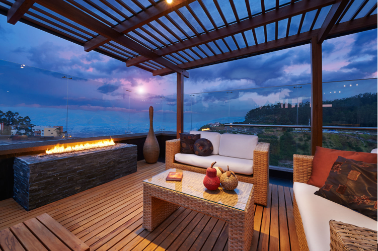 patio with roof, wood flooring, fireplace, rattan furniture