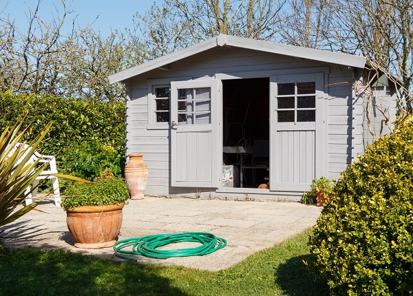 grey shed with plants and hose on foreground