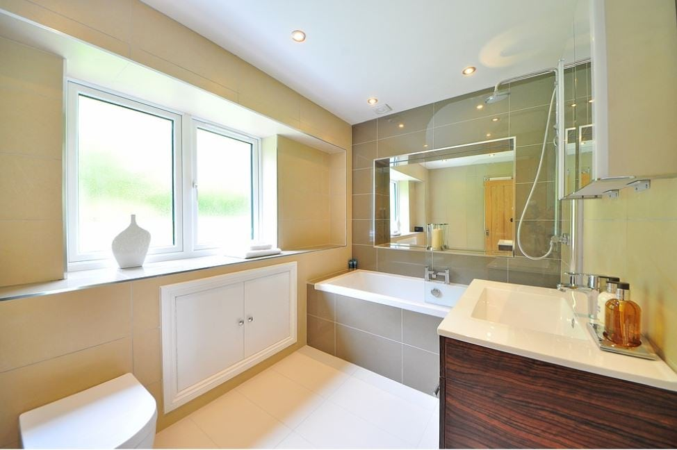 bathroom with white bath, yellow walls, mirror, vanity, rain shower and downlights